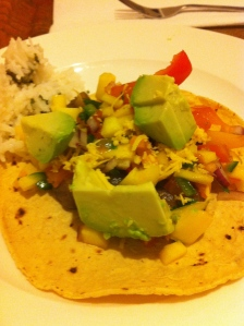 A corn tortilla, topped with beans, peppers, onions, mango salsa, and avocado!